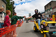 """Marc Kroetch, right, gives a drive-by high five to Stephen Loftis, left, on Kroetch's racing lawnmower """"Mow Heat Oh!"""" during the Big Back-In on Maine Street in Spirit Lake. Kroetch along with several others began the annual Father's Day tradition of the Big Back-In in Spirit Lake ten years ago as a way to fundraise for city projects.."""