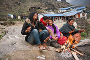 Female trekking guides and lodge owners laugh together around a fire outside the lodges at Deorali along the Annapurna Sanctuary Trek, Himalaya Mountains, Nepal. The guides work for 3 Sisters Adventure Trekking, a women owned company based in Pokhara that employs and empowers Nepali women.