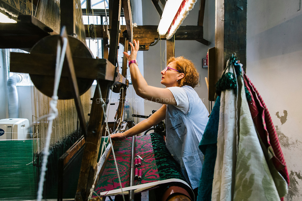 """FLORENCE, ITALY - 26 OCTOBER 2018: Luana Segreto, a weaver, is seen here working on a handloom dating back to the 1700s that can produce a mere 40 centimeters of fabric a day, here at the Antico Setificio Fiorentino, an ancient silk mill in central Florence, Italy, on October 26th 2018.<br /> <br /> The Antico Setificio Fiorentino is a silk mill, located in central Florence within view of the old city walls in the San Frediano neighborhood, that produces the kind of fabrics destined for city palaces and country estates. The mill was bought in 2010 by Stefano Ricci from the Pucci, with an eye to using it to produce fabrics for the launch of a new home collection<br /> <br /> Lined up in rows are the dozen looms that take the slender threads, by now dyed emerald and ruby and sapphire, and weave them into the textiles that form a part of the fabric of Florentine life.<br /> <br /> Silk was made in the city as far back as the 1300s, a commodity to trade for precious materials. In more recent times, the fabric in the gowns in """"Il Gattopardo"""" and """"Death in Venice"""" came from the mill, as did much of Maris Callas' wardrobe, robes for Popes, suits for Andre Bocelli, and Nelson Mandela's silk shirts (when he wore one for his audience with Queen Elizabeth II she reportedly remarked, """"that's a beautiful shirt."""") The carmine red curtains at the Villa Medici and the Tribune of the Uffizi were made here. The Presidential Suite at the city's Four Seasons Hotel is decked out in the mill's output, as are the walls of the room of the Czars at the Kremlin, and more than 100 red velvet chairs emblazoned with the Kremlin's golden crest.<br /> <br /> Back hundreds of years ago, in the Renaissance, most noble families had their own looms. But in 1786 the Grand Duke Pietro Leopoldo of Tuscany took all the looms of the private aristocratic families and put them in one place. They ended up at the Antico Setificio Fiorentino: six of them from the 1700s, hand looms that produce a mere 40 centim"""