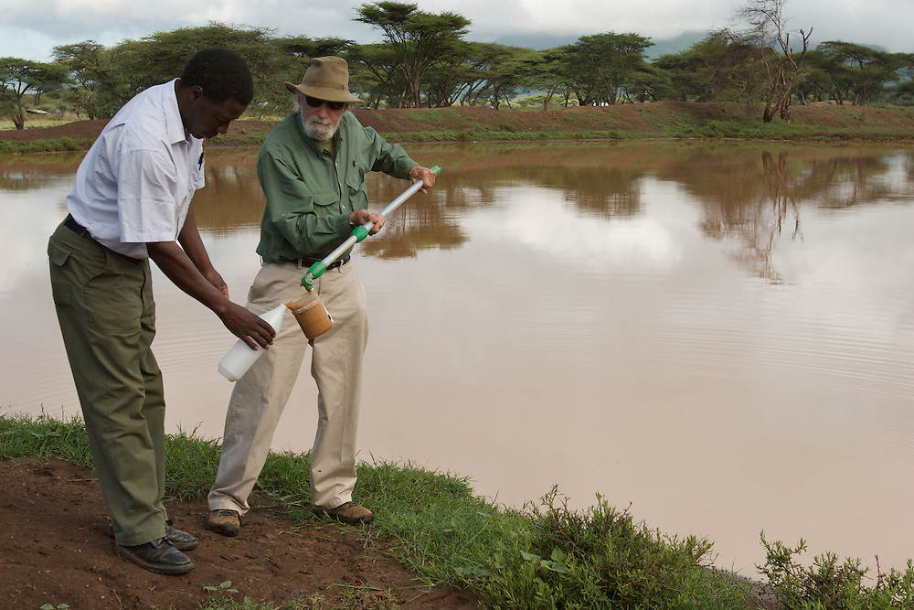 Researcher and volunteer pour water sample into container for lab work.