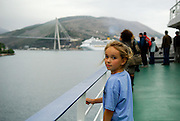 Child at railing of large ship in early morning light, with Cruise Liner and the Franjo Tudjman Bridge (Most Franja Tudjmana) in background. Dubrovnik, Croatia