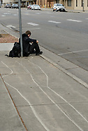 Man waiting for a bus. Lines on sidewalk. Loveland CO