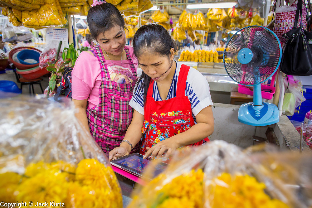 19 OCTOBER 2012 - BANGKOK, THAILAND:  Marigold vendors play card games on an iPad in the Bangkok Flower Market. The Bangkok Flower Market (Pak Klong Talad) is the biggest wholesale and retail fresh flower market in Bangkok.  The market is busiest between 3:30AM and 6AM. Thais grow and use a lot of flowers. Some, like marigolds and lotus, are used for religious purposes. Others are purely ornamental.       PHOTO BY JACK KURTZ