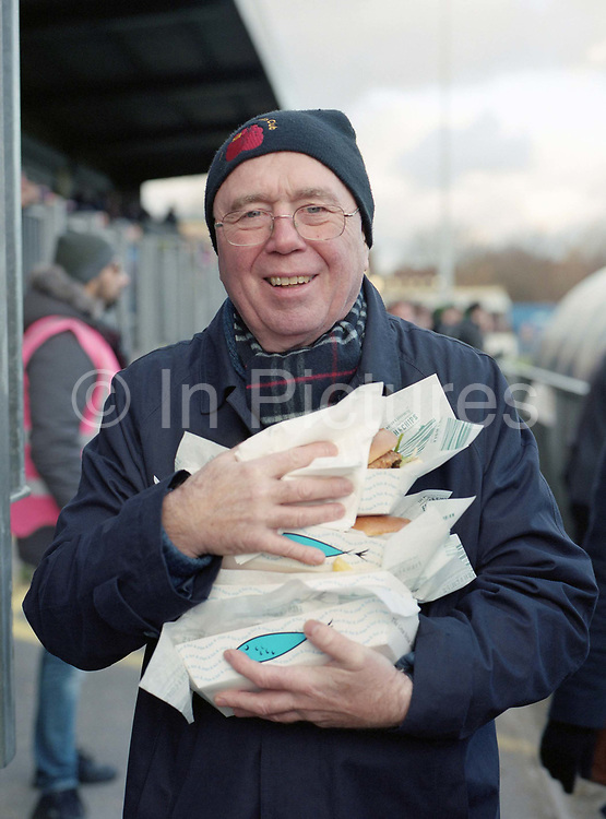 A DHFC fan loaded up burgers and fish and chips during the Dulwich Hamlet F.C. game vs Lowestoft Town F.C. at Champion Hill on 25th October 2017 in South London in the United Kingdom. Dulwich Hamlet was founded in 1893 and both teams play in the Isthmian League Premier Division, a regional mens football league covering London, East and South East England.