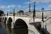 Seen from the southern bank of the river Thames is the architecture of Kingston Bridge where a pedestrian climbs its steps, on 7th November 2019, in Kingston, London, England. A crossing has existed at Kingston since ancient times and this version of Kingston Bridge was constructed by Herbert for £26,800 and opened by the Duchess of Clarence the future Queen Adelaide on 17 July 1828. Constructed from Portland stone, it comprises of five elliptical arches.