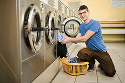 Young man filling up cloths in machine, smiling