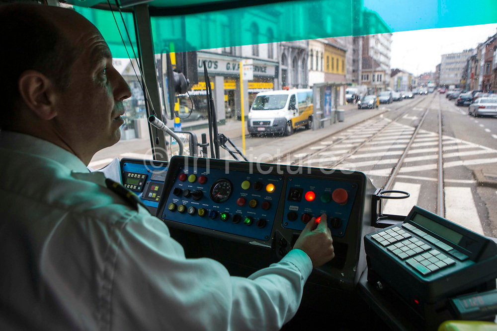 A Belgium tram controller drives his tram down a busy street in the city centre of Ghent. The trams have been modernized to use less electricity and become more sustainable public transport.