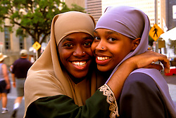 Stock photo of a pair of traditionally dressed women hug at the International Festival in downtown Houston Texas