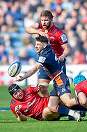 Charlie Shiel (#21) of Edinburgh Rugby looks to offload the ball as he is tackled by Rhys Marshall (#16) of Munster Rugby during the Heineken Champions Cup quarter-final match between Edinburgh Rugby and Munster Rugby at BT Murrayfield Stadium, Edinburgh, Scotland on 30 March 2019.