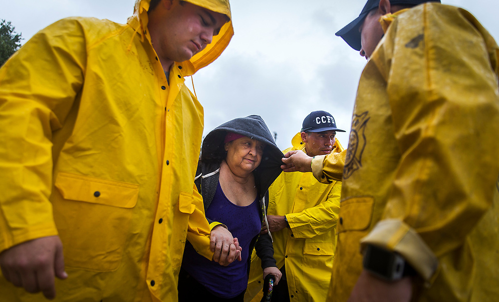 Corpus Christi firefighters help Guadalupe Guerra walk to a bus headed for San Antonio at an evacuation center on Friday, Aug. 25, 2017, in Corpus Christi, Texas. Hundreds of residents were evacuated by bus this morning as Hurricane Harvey is expected to make landfall on the Texas coast tonight or early Saturday morning as a category 3 hurricane. NICK WAGNER / AMERICAN-STATESMAN