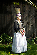 Marina, member of the Altländer Trachtengruppe von 1970 e. V., is wearing a traditional bridal gown in Jork, Germany on April 30, 2017.<br /> <br /> This traditional costume and the jewelry is original and from around the 1900s. The bridal gown is a replica. Until the wedding, girls and young women used to wear only black. They always covered her hair and it is said that most of the time the man found out the color of his wife's hair after the wedding.<br /> <br /> This is part of the series about Traditional Gowns from different regions of Germany, worn by young members of local dance groups and cultural associations that exist to preserve and celebrate the cultural heritage. The portraiture series is a depiction of an old era with different social values and religious beliefs in an antiquated civil society with very few of those dresses left.