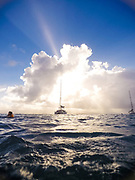 Boat at anchor in Guadloupe as the sun shines through a cloud, shot on GoPro