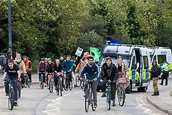 London, UK. 6 September, 2019. Climate activists take part in a Critical Mass bicycle ride as part of Stop The Arms Fair protests outside ExCel London on the fifth day of a week-long carnival of resistance against DSEI, the world's largest arms fair. The fifth day of protests was themed as Stop The Arms Fair: Stop Climate Change in order to highlight links between the fossil fuel and arms industries.