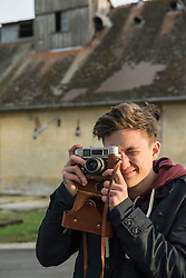 Young man clicking pictures with retro styled camera, Munich, Bavaria, Germany