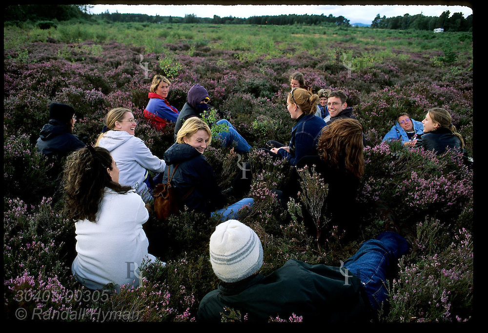 Circle of students in heather patch at Culloden Moor discuss tragic battle fought here on April 16, 1746; Inverness, Scotland.