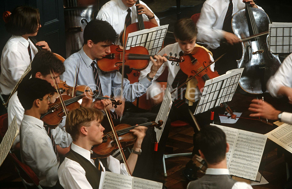Schoolboys from the City of London School play string instruments during a public performance of classical music. The young orchestra is performing at St. James Garlickhythe, a city of London church redesigned by Sir Christopher Wren after its destruction in 1666. Showing great concentration and passion for their music, the violinists and cellists play with great skill for such young players. We see their copyrighted sheet music attached to the stands, guiding them through the classical pieces listened to by an unseen audience. There is a slight blurring to arms and hands as their bows pass over the bridges of their instruments. <br /> .