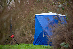 © Licensed to London News Pictures. 12/12/2019. Milton Keynes, UK. A forensic tent sits in a wooded area in the Fishermead area after a man was stabbed. Thames Valley Police has launched a murder investigation following the death of a man in Milton Keynes. Police and South Central Ambulance Service attended a woodland in Fishermead, Milton Keynes at around 15:20GMT on Wednesday 11th December 2019 after a report of an altercation between a group of men, during which a man had been stabbed. The victim, a man aged in his twenties died at the scene. Photo credit: Peter Manning/LNP
