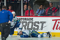 REGINA, SK - MAY 19:  Artyom Minulin #5 kneels beside Tyler Steenbergen #17 of Swift Current Broncos as he lay on the ice after a check into the boards against the Acadie-Bathurst Titan at the Brandt Centre on May 19, 2018 in Regina, Canada. (Photo by Marissa Baecker/CHL Images)