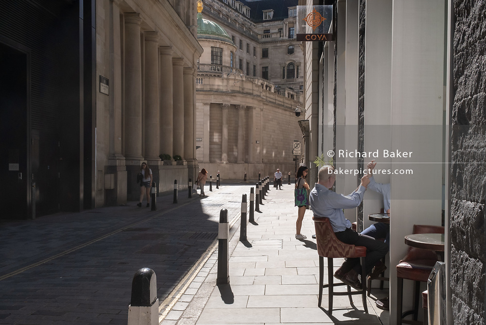 A city worker sits in afternoon sunshine on Throgmorton Street during the Coronavirus pandemic in the City of London, the capital's financial district, on 30th July 2020, in London, England.  city worker sitting on a bar stool outside a pub on Throgmorton Street during the Coronavirus pandemic in the City of London, the capital's financial district, on 30th July 2020, in London, England.