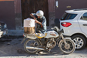A Mexican man unloads a barrel of homemade ice cream from the back of his motorcycle March 23, 2018 in San Miguel de Allende, Mexico.