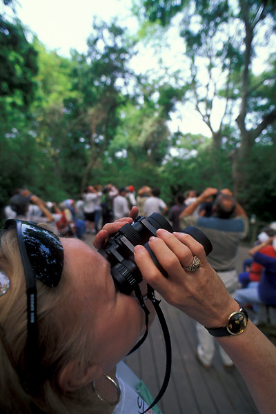 A close up of a female bird watcher with binoculars