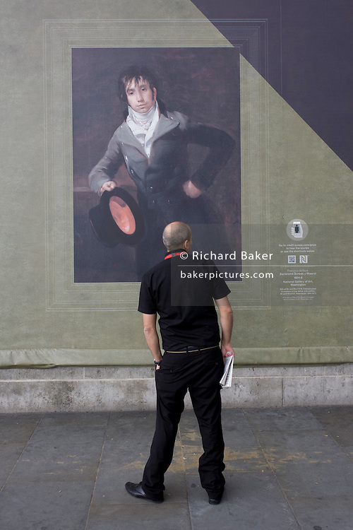 A man on the street reads about a Goya portrait, sponsored by Credit Suisse and advertised on a construction hoarding outside the National Portrait Gallery.