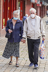 © Licensed to London News Pictures. 13/08/2020. Oldham, UK. A couple wear face coverings as they walk through the streets of Oldham this afternoon.  In recent weeks, the town of Oldham has seen a rapid increase in new coronavirus cases. Photo credit: Ioannis Alexopoulos/LNP