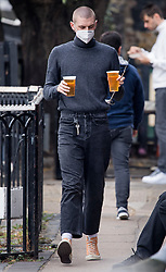 © Licensed to London News Pictures. 24/09/2020. London, UK. A man wearing a face mask carrying beer at a pub in Camden, North London, on the first day that pubs will be forced to close at 10pm in an attempt to prevent the spread of COVID-19. Chancellor Rishi Sunak today outlined a series of financial packages to help business through new lockdown measures. Photo credit: Ben Cawthra/LNP