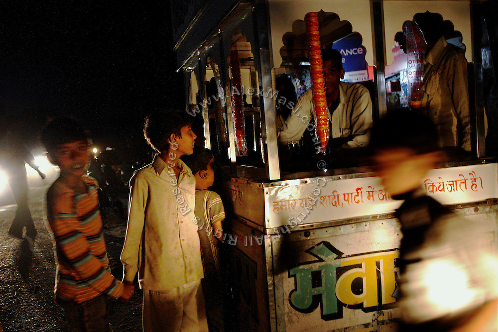 Children are lining up for an ice-cream on the road during a warm evening in the village of Barnawa, pop.6000, Baghpat District, Uttar Pradesh, India, located along the banks of the severely polluted Hindon river, on Thursday, Apr. 17, 2008.