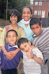 Group of young children standing together smiling,