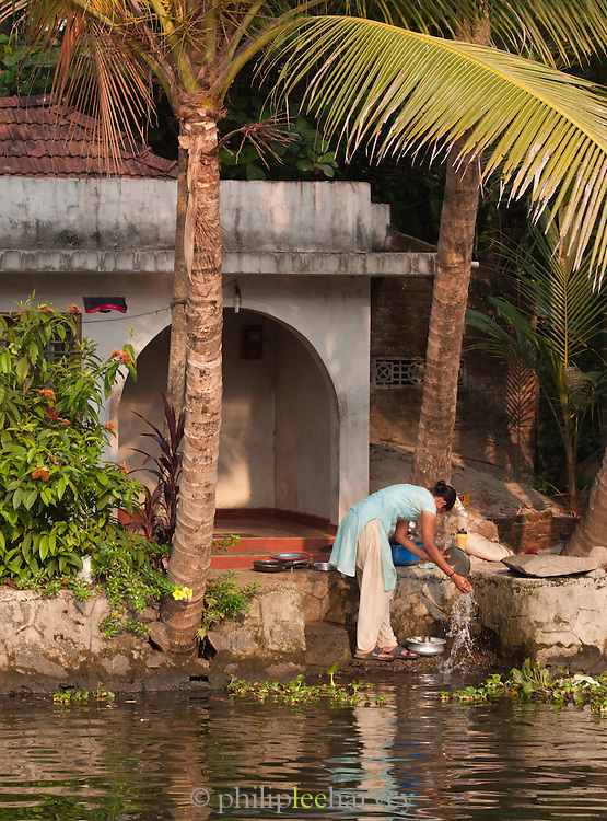 A woman washing dishes in the waters of the Kerala Backwaters, near Alappuzha, India