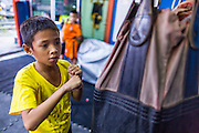 """18 DECEMBER 2104 - BANGKOK, THAILAND: A boy works out at the Kanisorn boxing gym. The Kanisorn boxing gym is a small gym along the Wong Wian Yai - Samut Sakhon train tracks. Young people from the nearby communities come to the gym to learn Thai boxing. Muay Thai (Muai Thai) is a Thai fighting sport that uses stand-up striking along with various clinching techniques. It is sometimes known as """"the art of eight limbs"""" because it is characterized by the combined use of fists, elbows, knees, shins, being associated with a good physical preparation that makes a full-contact fighter very efficient. Muay Thai became widespread internationally in the twentieth century, when practitioners defeated notable practitioners of other martial arts. A professional league is governed by the World Muay Thai Council. Muay Thai is frequently seen as a way out of poverty for young Thais and Muay Thai camps and schools are frequently crowded. Muay Thai professionals and champions are often celebrities in Thailand.     PHOTO BY JACK KURTZ"""
