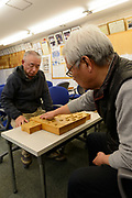 Katsuo Oshino (left) and Yoshio Muraoka of the Tendo City Shogi Club playing shogi. Tendo, Yamagata Prefecture, Japan, February 20, 2018. The city of Tendo in Yamagata Prefecture is famous for its shogi (Japanese chess) playing pieces. Production started early in the 19th century and Tendo still produces over 95% of the Shogi pieces made in Japan.