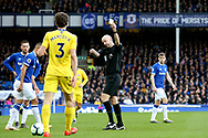 Chelsea defender Marcos Alonso  is shown a yellow card by Referee Anthony Taylor during the Premier League match between Everton and Chelsea at Goodison Park, Liverpool, England on 17 March 2019.
