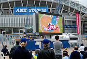 Two policewomen join the crowd watching the 2008 Rugby League Grand Final on a big screen set up outside Olympic Stadium. Sydney, Australia