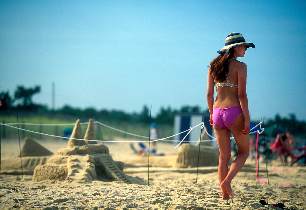An unidentified woman strolls past one of the entries at the annual sand castle contest, Saturday, Aug. 1, 2015, in Rehoboth Beach, Del. (Photo by D. Ross Cameron)