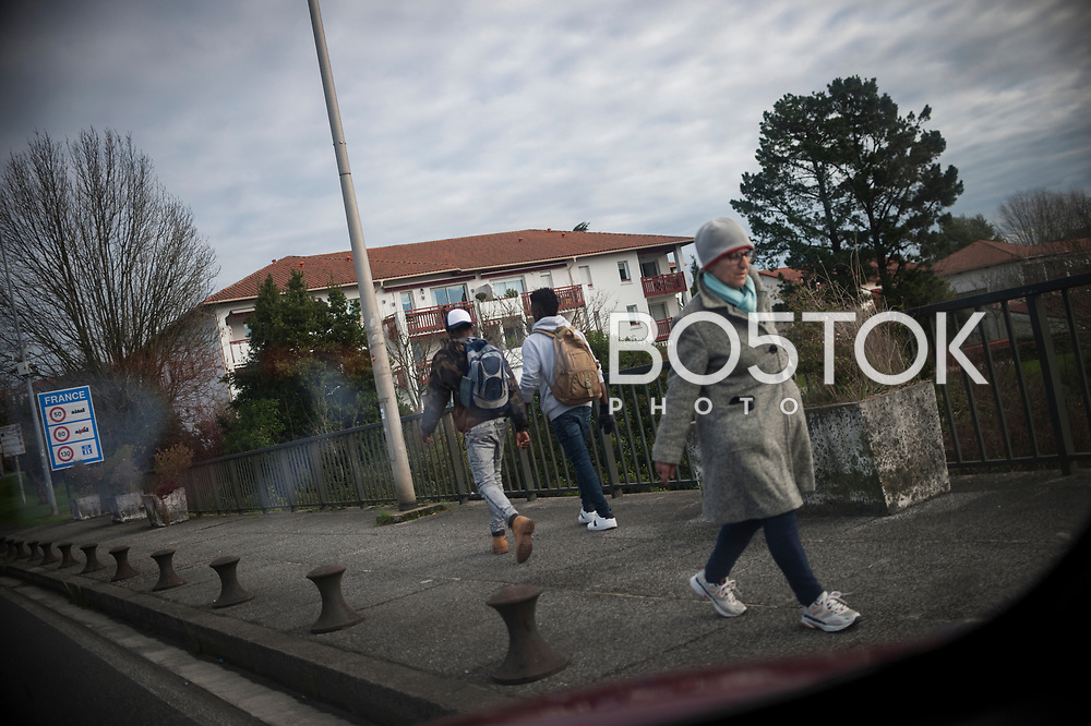 Two African migrants heading to France to cross the Spanish french border walking along Santiago bridge.  Irun (Basque Country). December 20, 2018. As the number of migrants arriving on the coasts of southern Spain incresead, more and more migrants are heading north to the border city of Irun. (Gari Garaialde / Bostok Photo)