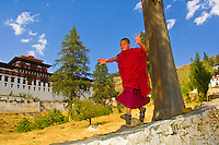 Novice monk running down wall in front of the Paro Dzong during the Paro Tsechu (festival), Paro, Bhutan