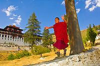 Novice monk running down wall in front of the Paro Dzong during the Paro Tsechu (festival), Paro, Bhutan