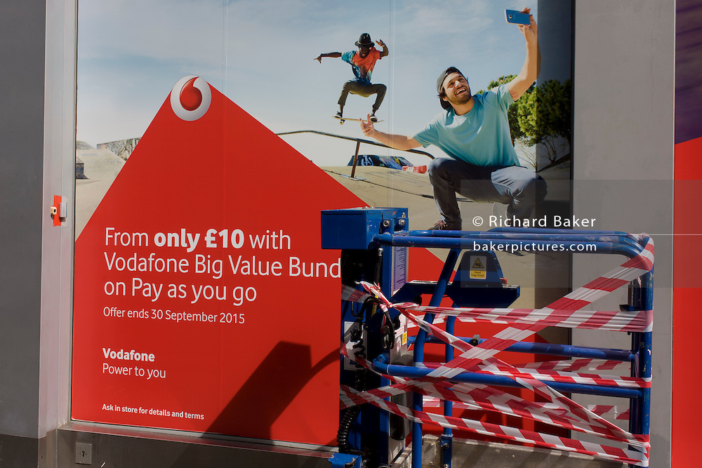 Exuberant youth taking selfies in an ad for Vodafone with a taped up construction cage in central London.