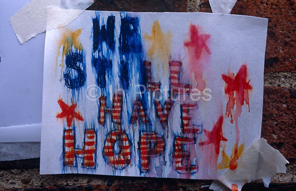 Days after the September 11th attacks in New York and Washington DC, posters starting appearing at strategic locations in Manhattan that either showed the faces of missing citizens, lost in the ruins of terrorist devastation or with patriotic rhetoric expressing hope, fate or anger and retribution as Americans sought to express their emotions and unity. But after overnight rain, the inks and dyes of home-printed pictures streaked and ran obliterating these messages and victims' faces. DNA samples were taken at the Armory so human remains might be identified so it was a point of focus for those with missing relatives who attached thousands of posters to walls with pictures and messages to loved-ones in the hope of being reunited.