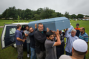 Amin Alsaloum (front), 27, carries his father's casket from hearse to grave with the help of brother Momen (second from L), 22, and members of their mosque community at a cemetery in Tampa, Florida, U.S. Riad Alsaloum's body went from hospital to funeral home to mosque to cemetery in a matter of hours. Islamic funeral customs dictate that the deceased should be buried as soon as possible.