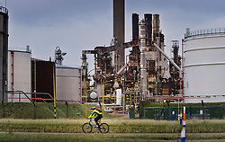 A cyclist rides past the Petroplus Holdings AG oil refinery, at the Port of Antwerp, in Antwerp, Belgium, Friday, Jan. 6, 2012. (Photo © Jock Fistick)