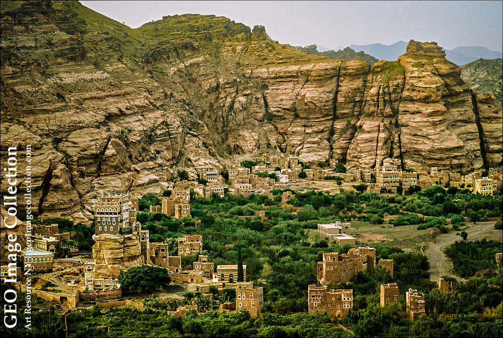 """Along a dried riverbed in a valley called Wadi Dahr lies the Dar al-Hajar or """"Rock Palace (lower left), a """" five-story royal structure located near Sana'a, capital of Yemen. The palace, popular with tourists util civil war engulfed Yemen, seems to grow out of the rocks on which it is constructed."""