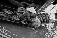 Woman washing baskets in the Thu Bon river in Hoi An.
