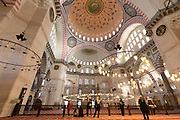 Tourists wearing scarves in interior of Suleymaniye Mosque in Istanbul, Republic of Turkey