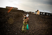 Jeanine Kahindo, 28, walks through lava rocks in the Majengo neighborhood in Goma, Eastern Democratic Republic of Congo on Saturday December 20, 2008. Originally from Kikumba, she fled six weeks ago when violence broke out, her brother in law killed during his sleep. Her husband and herself pay 5$ to rent a small house in Goma where they live with their children. A few days ago, she says, soldiers looted the neighbors' home in broad daylight, taking radios, cookware, matresses, everything.