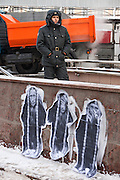Moscow, Russia, 04/02/2012..A Russian policeman standing behind graffiti depicting Prime Minister Vladimir Putin as the three monkeys ?Hear no evil, see no evil, speak no evil? watches as tens of thousands of demonstrators march in central Moscow and protest against election fraud and Prime Minister Vladimir Putin in temperatures of -20 centigrade. Organisers claimed an attendance of 130,000 despite the bitter cold.
