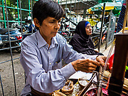 25 JUNE 2017 - BANGKOK, THAILAND: A candy vendor sells sweets to children in front of Ton Son Mosque before Eid al-Fitr services. Eid al-Fitr is also called Feast of Breaking the Fast, the Sugar Feast, Bayram (Bajram), the Sweet Festival or Hari Raya Puasa and the Lesser Eid. It is an important Muslim religious holiday that marks the end of Ramadan, the Islamic holy month of fasting. Muslims are not allowed to fast on Eid. The holiday celebrates the conclusion of the 29 or 30 days of dawn-to-sunset fasting Muslims do during the month of Ramadan. Islam is the second largest religion in Thailand. Government sources say about 5% of Thais are Muslim, many in the Muslim community say the number is closer to 10%.    PHOTO BY JACK KURTZ