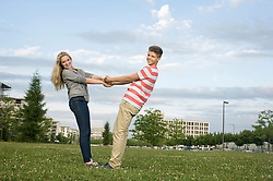 Portrait of teenage couple holding hands in park, smiling